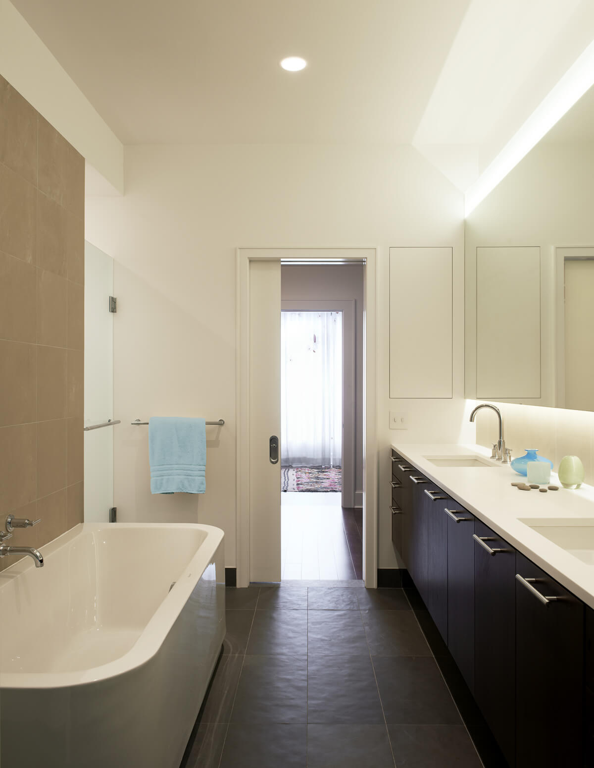 modern bathroom with lighting band etched into vanity mirror