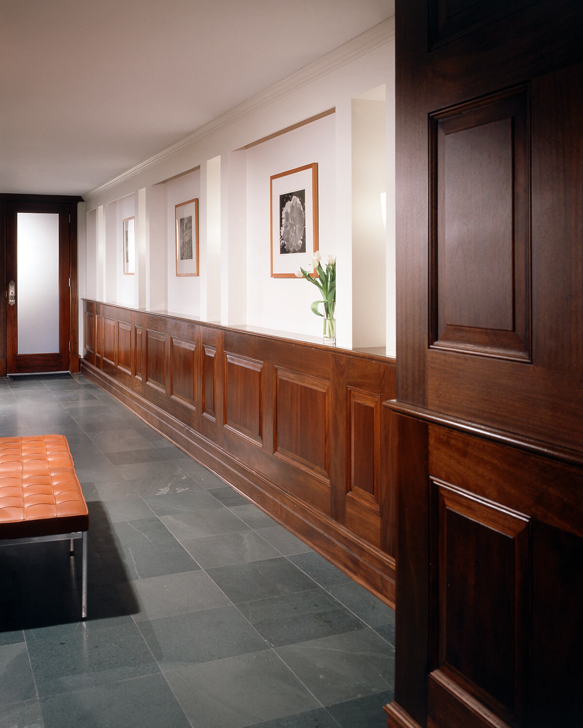 Paneled wainscot, etched glass doors, and slate tile floors in a grand limestone row house.