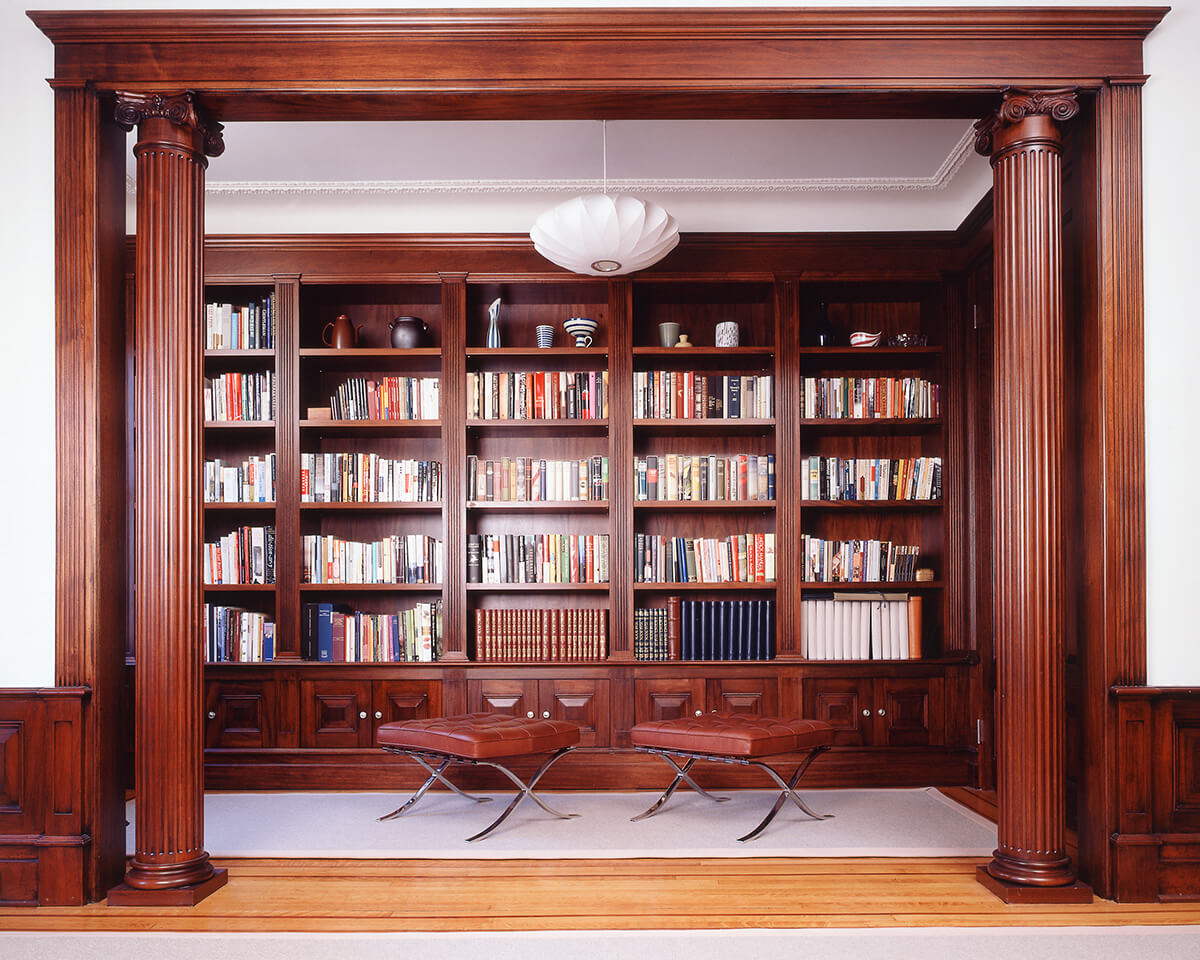 Replicated traditional library millwork contrasts with modern fixtures and furnishings in grand limestone row house.