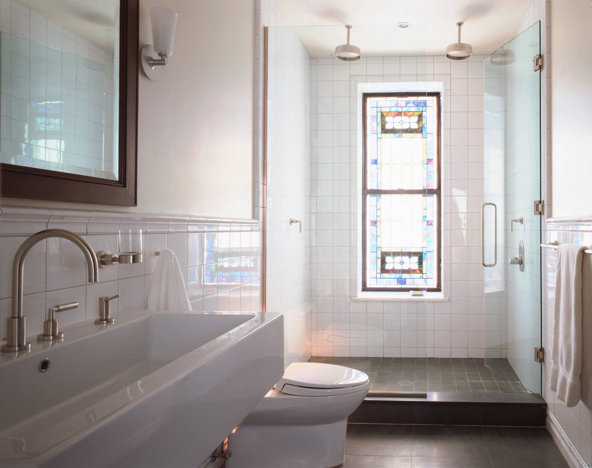 Refurbished stained-glass window in a minimalist bathroom.