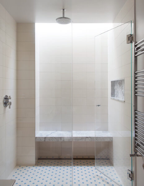 A skylight washes daylight down a shower wall to a floating stone bench. Beneath it is a linear floor drain your feet never touch.