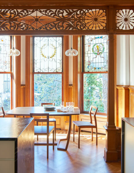 New soapstone slabs and inlaid floors crisply contrast with old filigree in the handsome kitchen of this Prospect Park West house.