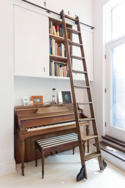 Rolling ladder over a player piano in this quirky apartment by Delson or Sherman Architects