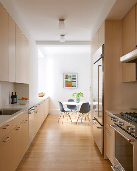 Seamless ash cabinetry smoothes out a bumpy kitchen in this West End Avenue Apartment.