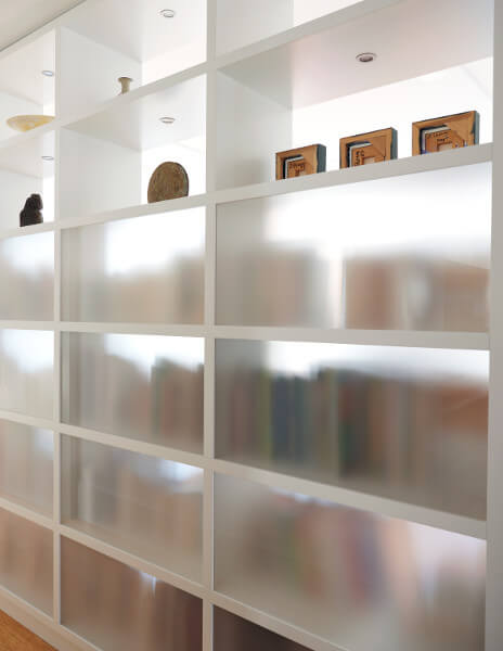 Translucent panels back an integrated bookshelf in this West End Avenue Apartment.