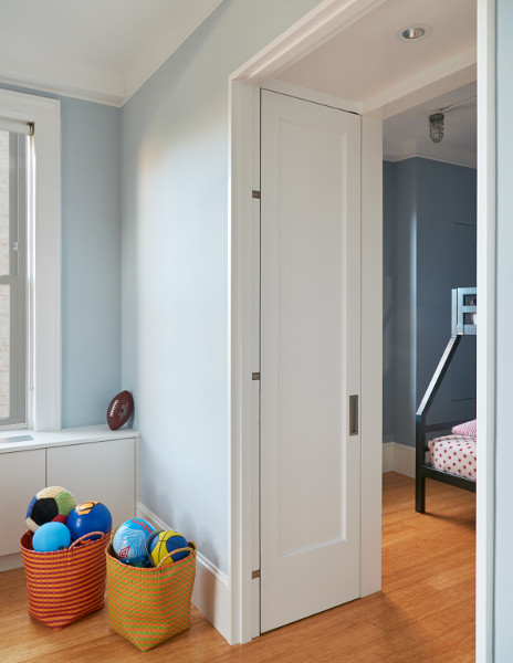 Room-dividing doors fold flush for a graceful transition between playroom and kids' bedroom in this West End Avenue apartment.