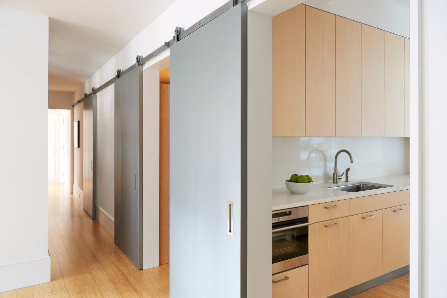 Metallic barn doors slide along a shared track this West End Avenue Apartment.