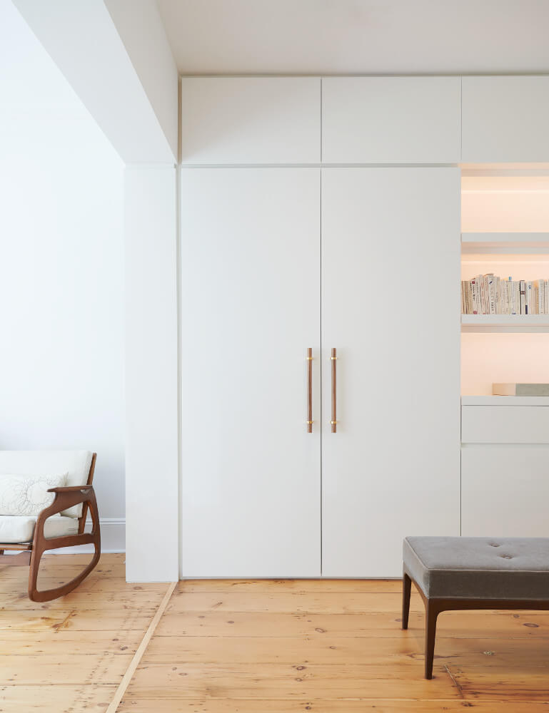 The master suite revolves around an oversized dressing room in minimalist high-gloss white. Door pulls are walnut and brass.