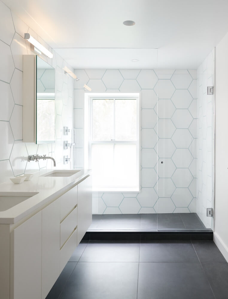 In the bathrooms, bold patterns and textures play against crisp detailing. Wall tile of oversize hexagons and a stone slab floor.
