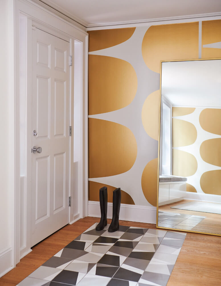 The mudroom combines an over-scaled wallpaper pattern, an inlaid tile floor, and sleek built-ins.