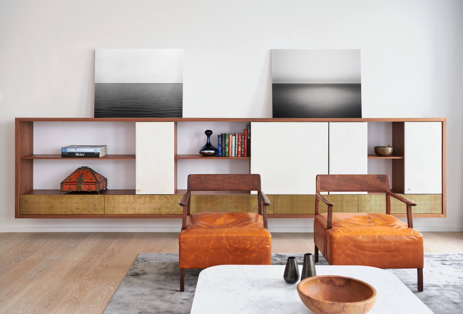 Custom built-in cabinetry made of leather and brass panels hides the TV.
