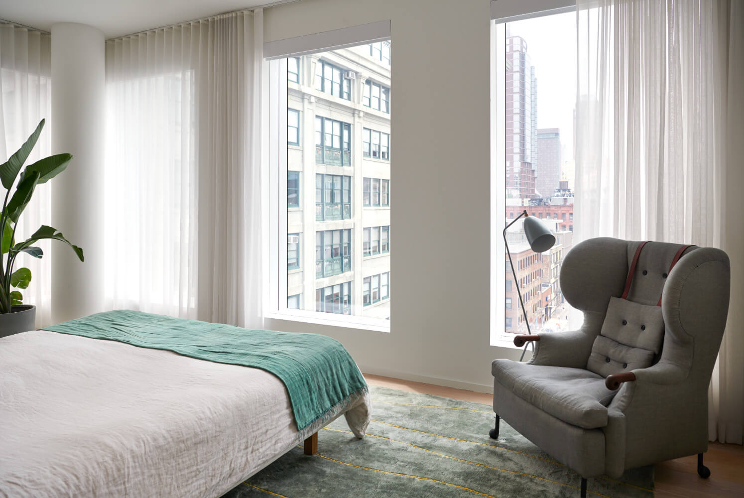 In the master bedroom of this DUMBO apartment, a new rug and relocated furnishings make the space both cozy and thrilling.