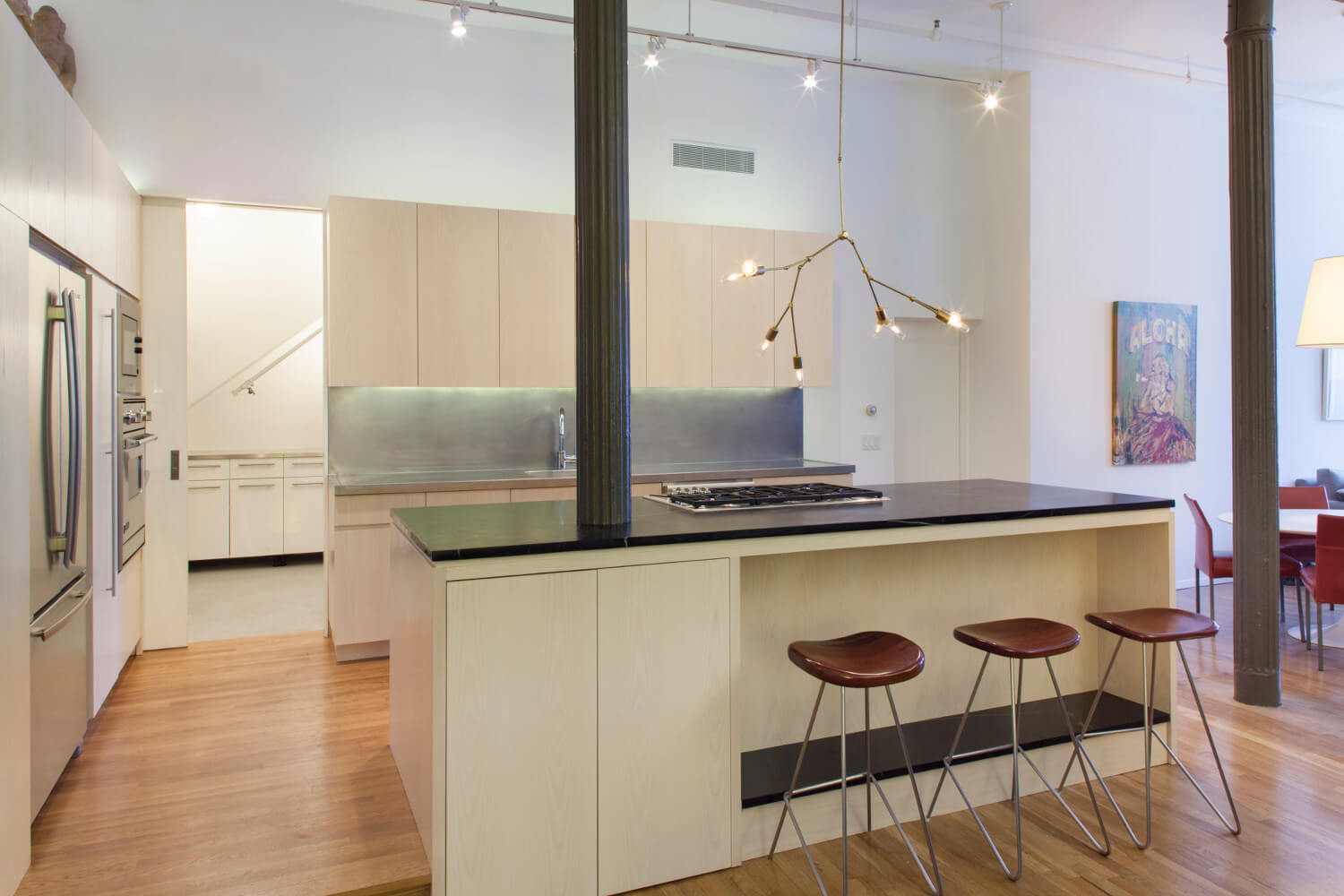 Sleek kitchen of Tribeca Loft has cabinetry of white-stained ash and countertops of soapstone and stainless steel.