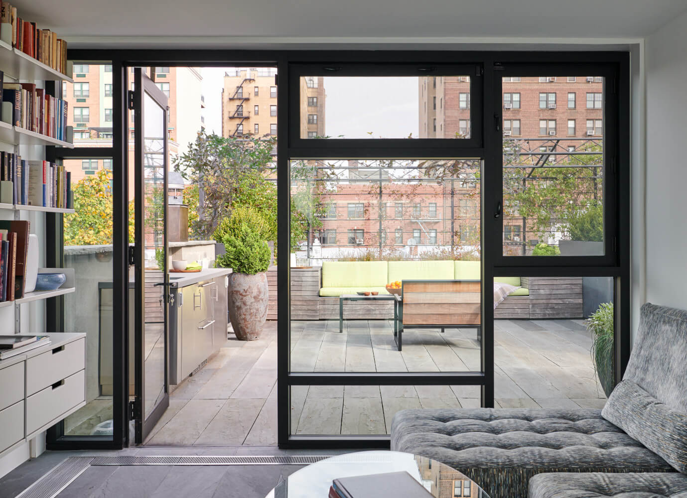 The rooftop sunroom of the Park Slope addition looks out through Mondrian mullions to a large roof deck.