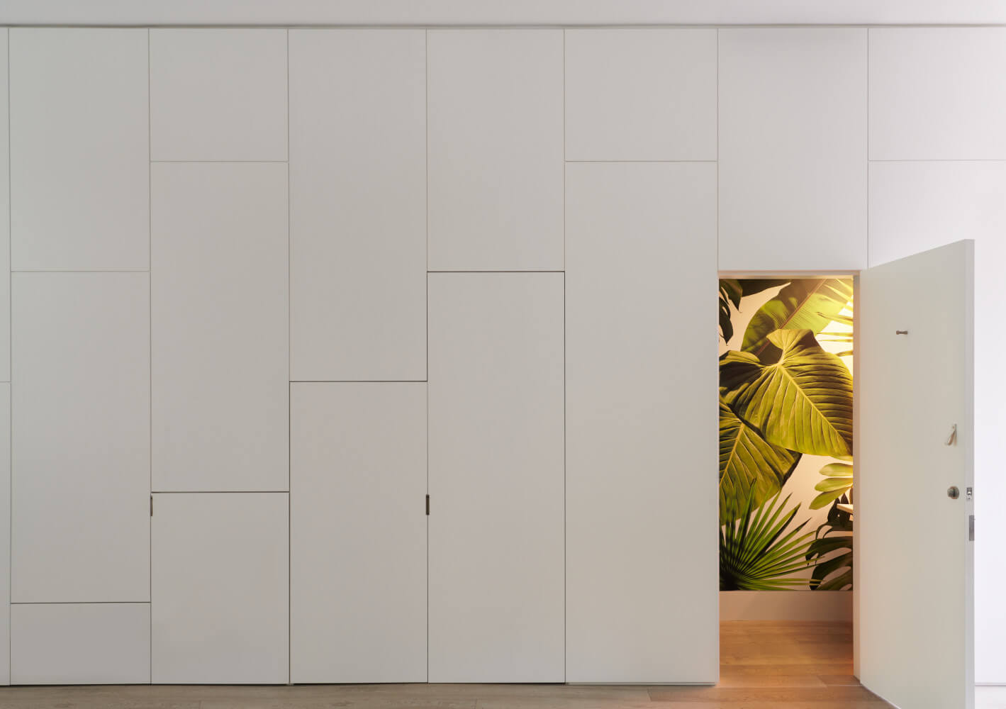 wall of white lacquer panels conceals a pantry, a coat closet, and a verdant powder room.