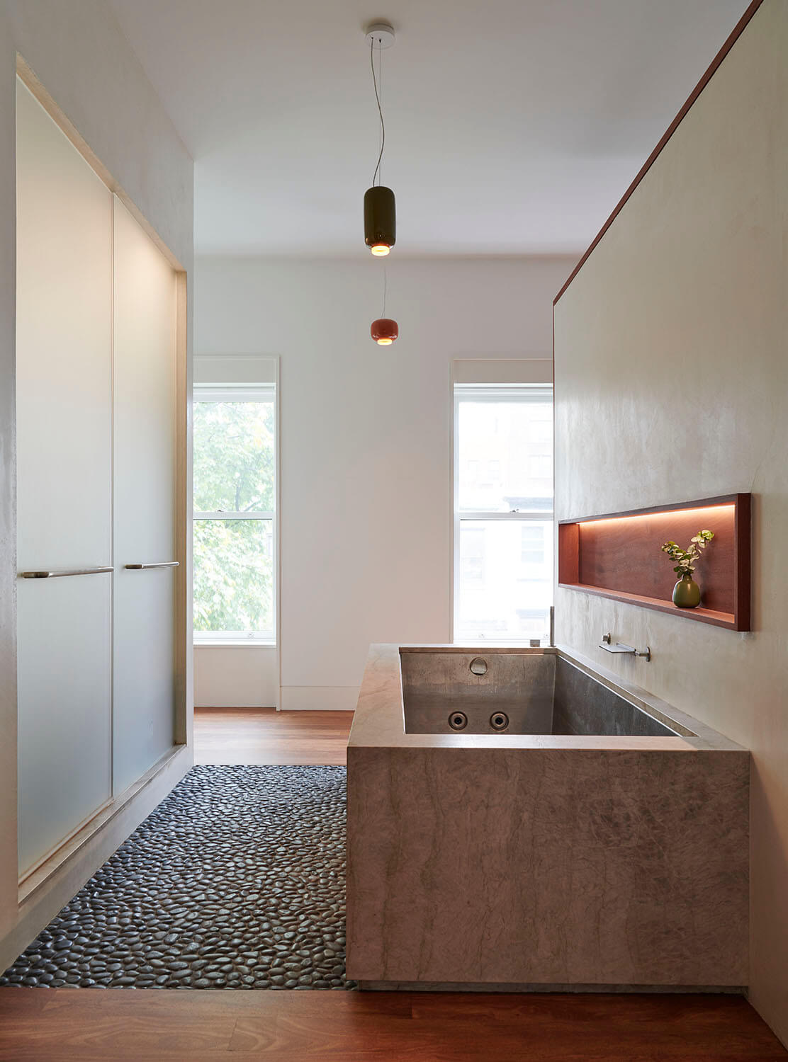 The parents' bathroom of this Park Slope addition has an oversized stainless steel hot tub wrapped in limestone and a floor of black pebbles.