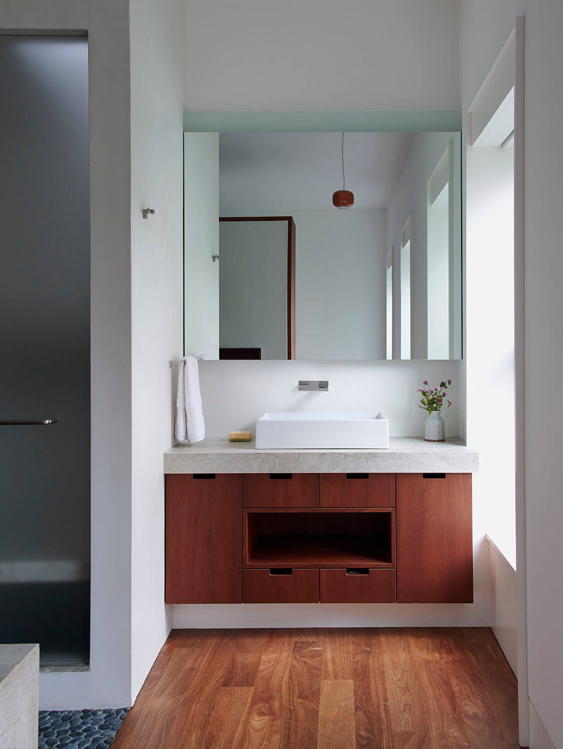 The parents' bathroom of this Park Slope addition has his and hers vanities flanking the walk-in shower.