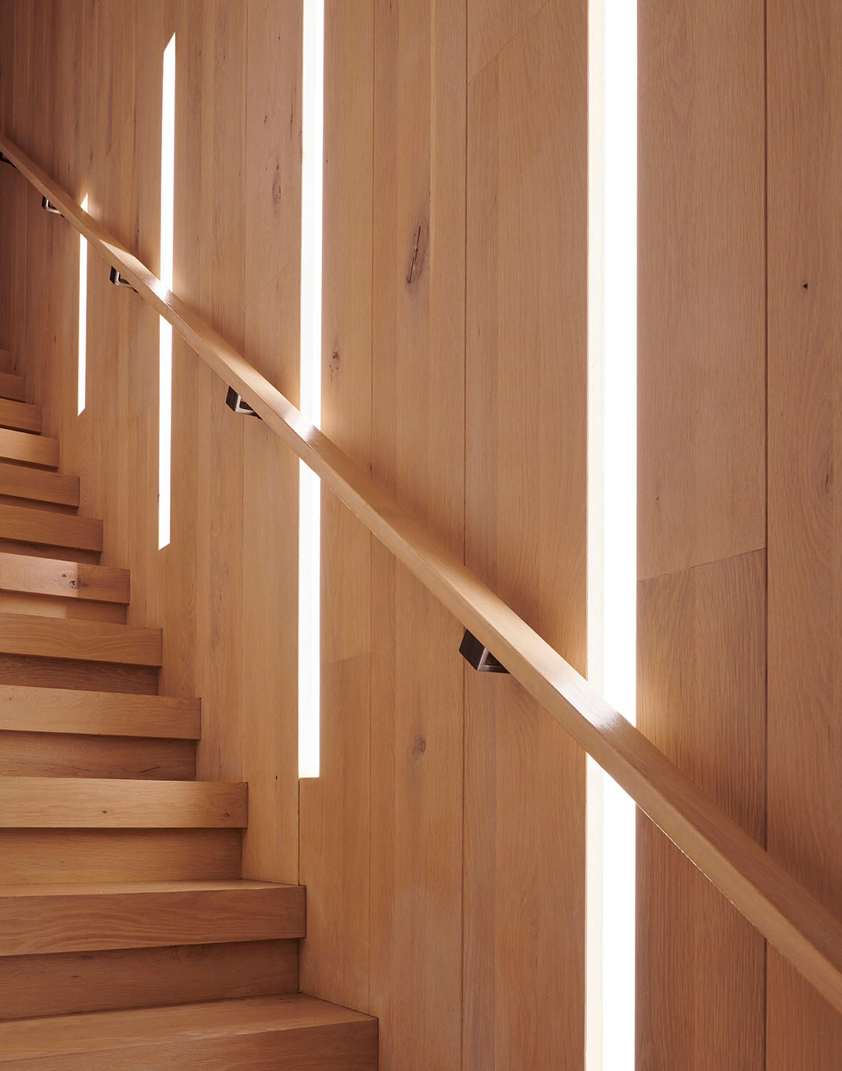 In this Park Slope addition, solid oak stair treads first cantilever from the wall, then turn up 90° to form a balustrade, here backlit with LEDs..