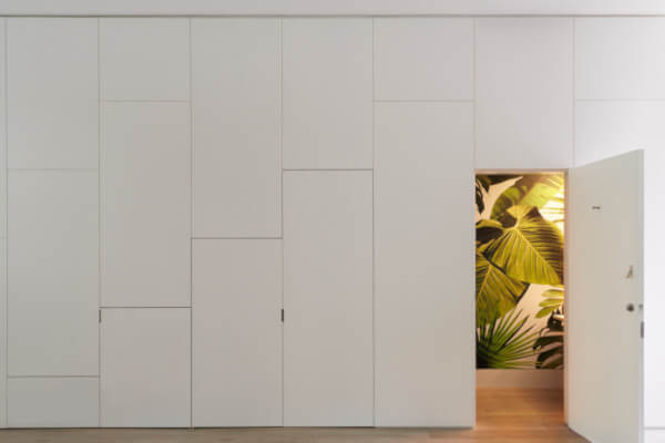 wall of white lacquer panels conceals a pantry, a coat closet, and a verdant powder room